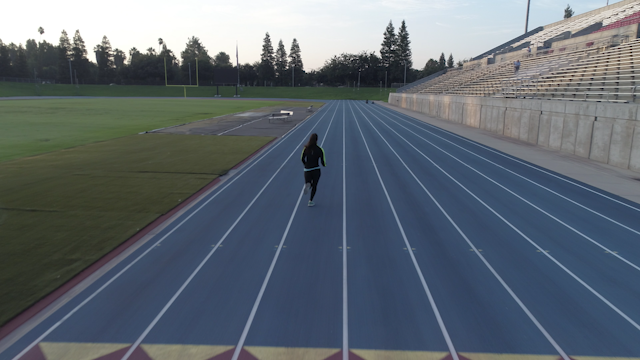 A woman is running along a track in a stadium thumbnail
