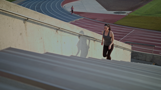 A woman is running up steps in a football stadium thumbnail