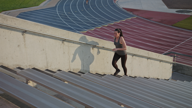 A woman jogs up stadium stairs thumbnail