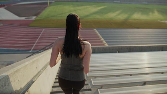 A woman jogs down stadium stairs thumbnail