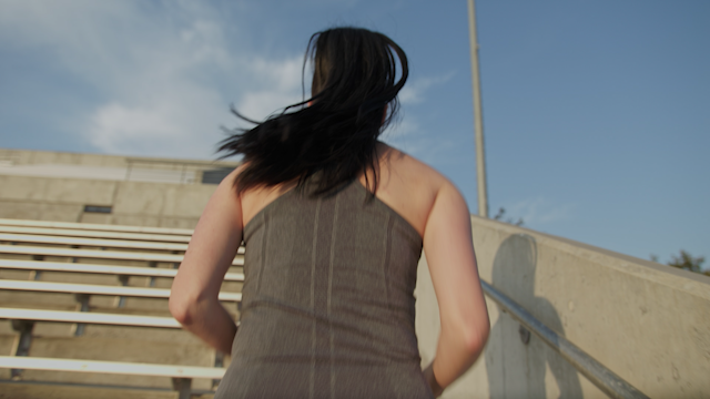 A woman is jogging up steps in a football stadium thumbnail