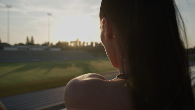 A woman looks out over a stadium while stretching thumbnail