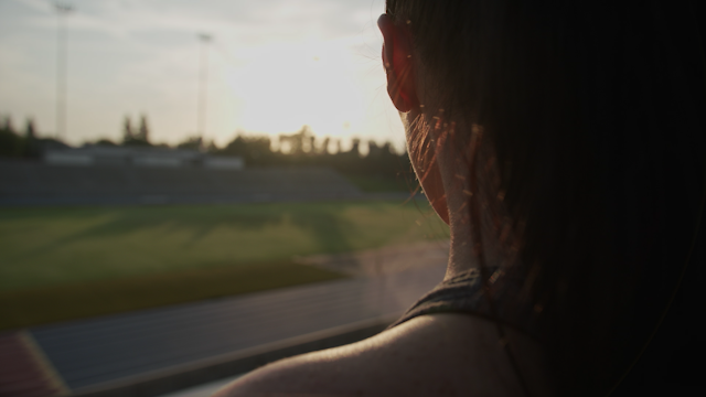 A woman looks out over a football stadium thumbnail