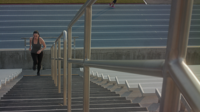 A woman runs up the stairs of a football stadium thumbnail