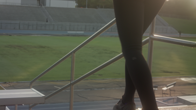 A woman is jogging down the stair steps in a stadium thumbnail