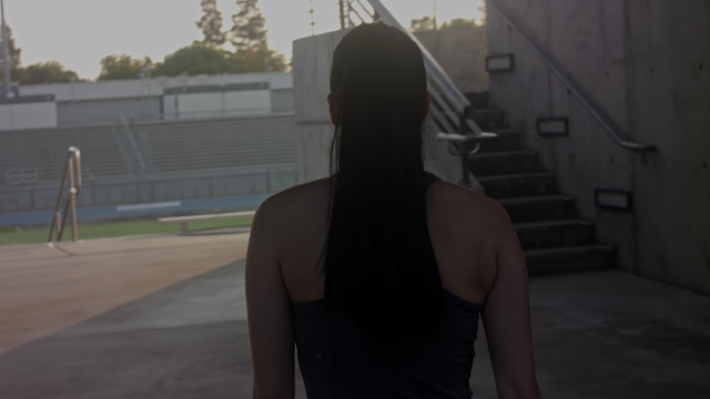 A woman walks out into the light inside a football stadium thumbnail