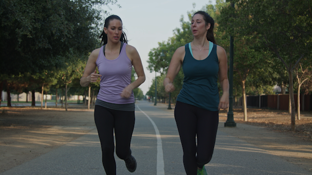 Two friends are jogging down a paved pathway thumbnail