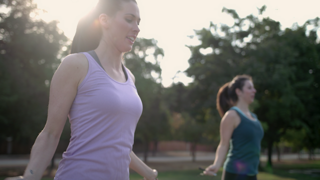 Two women are jumping rope in a park in the morning thumbnail