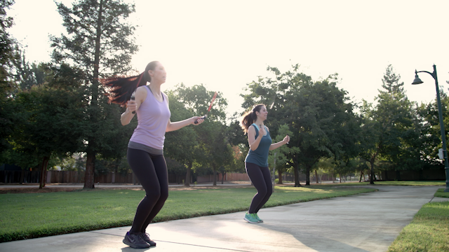 Two friends are jumping rope in a park thumbnail