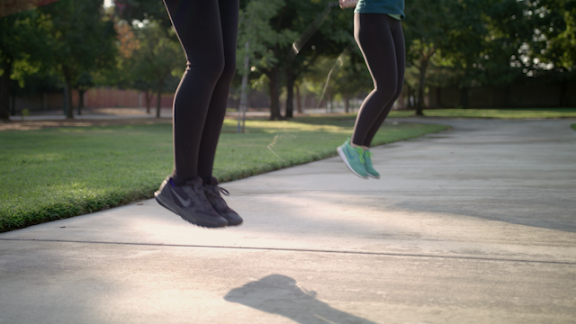 Two friends are jumproping in a park thumbnail