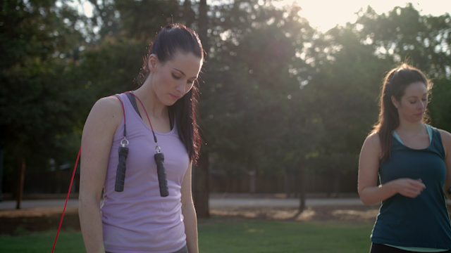 Two women are starting to jump rope in a park thumbnail