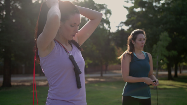 Two women prepare to jump rope in a park thumbnail