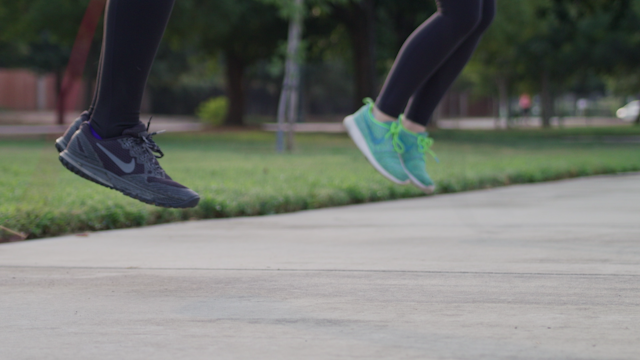 Feet are jump roping in a park thumbnail