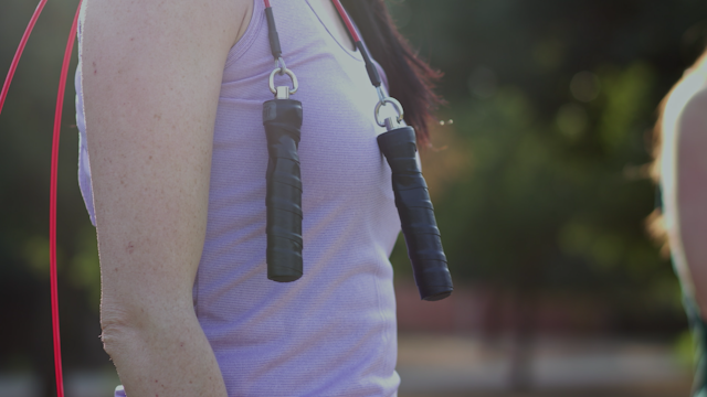 A jump rope is hanging over a woman's shoulder thumbnail