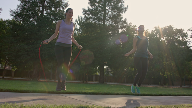 Two women jump rope together in a public park thumbnail