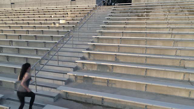 A woman runs up and down stadium steps thumbnail