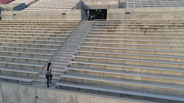 A woman is running up and down stadium steps thumbnail