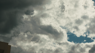 Clouds roll and formulate over a building in a timelapse thumbnail