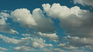 Clouds are rolling by through a blue sky thumbnail