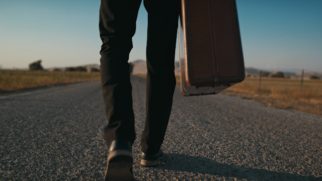 A man walks down a road with a suitcase thumbnail
