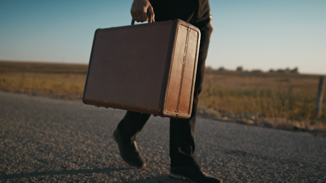 A well dressed man walks down a road with a suitcase at sunset thumbnail