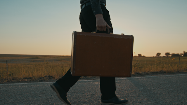 A man walks down a road with a suitcase at sunset thumbnail
