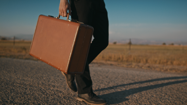 A man walks down a country road with a suitcase thumbnail