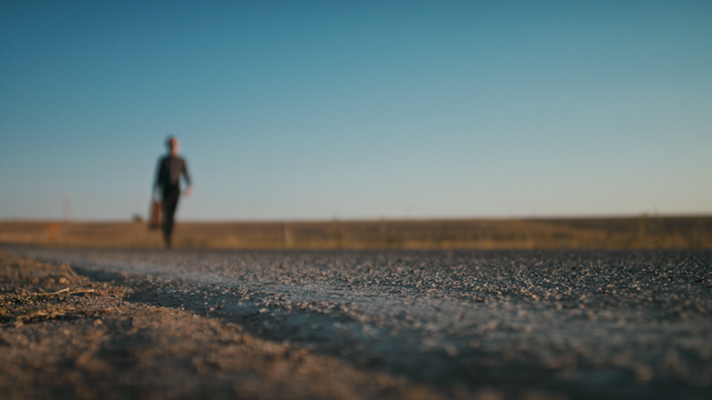 A well dressed man walks down a road holding a suitcase thumbnail