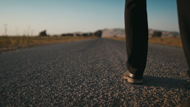 A man is walking down a country road with a suitcase thumbnail