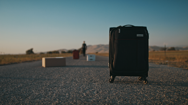 Luggage is sitting on a country road while a man approaches thumbnail