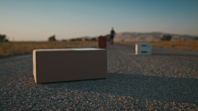 A package is sitting on a country road while a man approaches thumbnail
