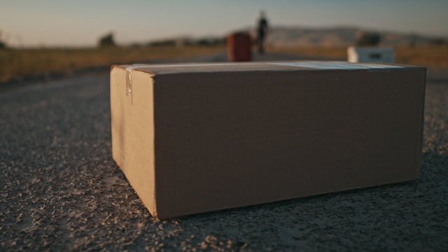 A box is sitting on a country road while a man approaches thumbnail
