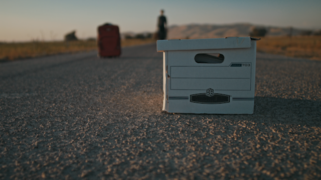 A file box is sitting on a country road while a man approaches thumbnail
