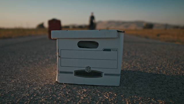 A file box sits on a country road while a man approaches thumbnail