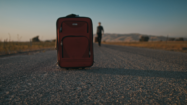 A red suitcase is sitting on a country road while a man approaches thumbnail