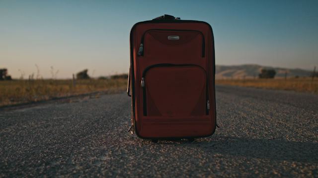 A red suitcase sits on a country road while a man approaches thumbnail
