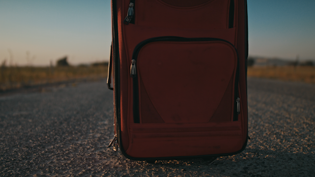A red suitcase is sitting on a country road while a man slowly approaches thumbnail