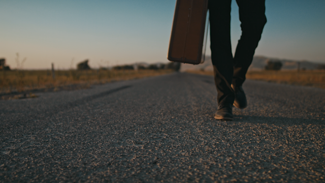 A man walks on a country road with a suitcase and stops thumbnail