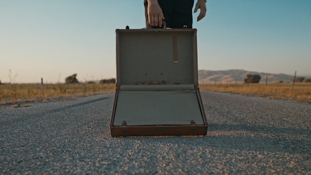 A man stands on a country road holding open and empty suitcase thumbnail