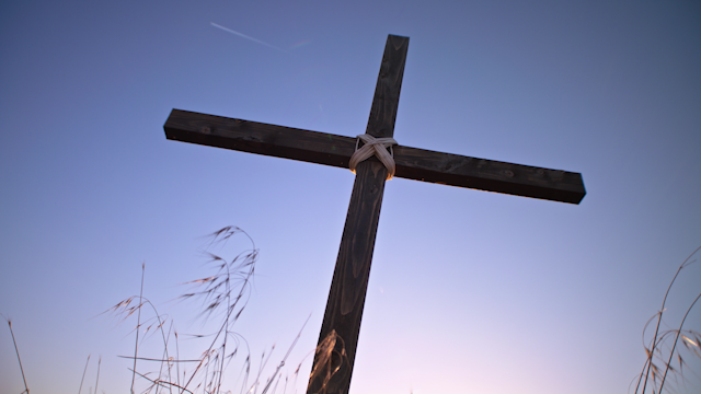 A cross stands in a field at sunset thumbnail