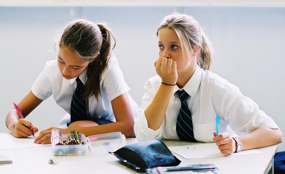 Candid Photograph in Class of two young students taking notes. Appleby College, Oakville Ontario