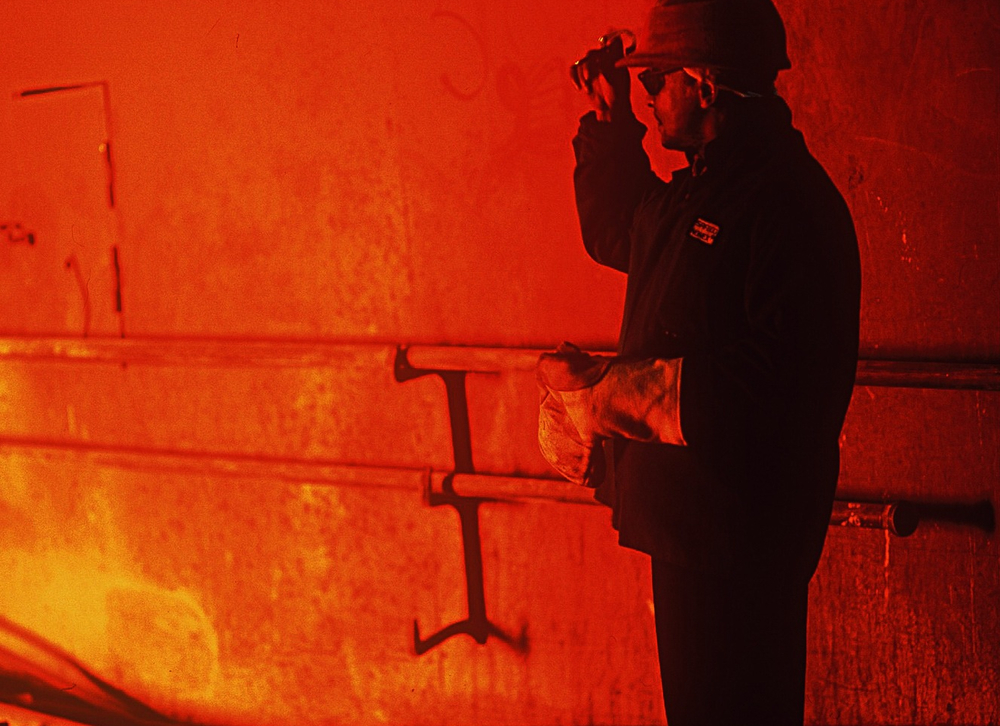 steel worker, dramatic silhoutte, red fire background