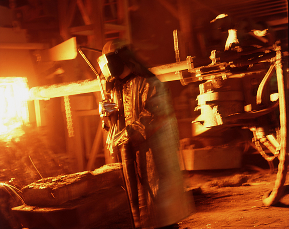 Dramatic Colour Shot of Steel Worker Checking Blast Furnace