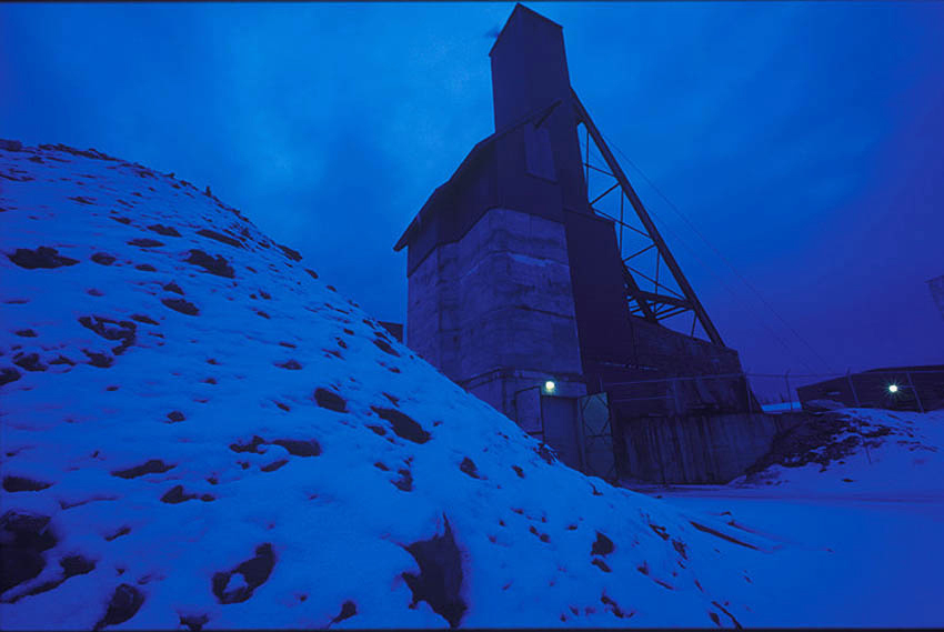 Dramatic dusk shot of a mining shaft, snow in foreground, mining shaft in background