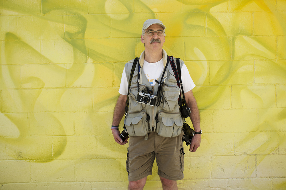environmental portrait, photographer with six time cameras, vibrant yello graffiti  wall.