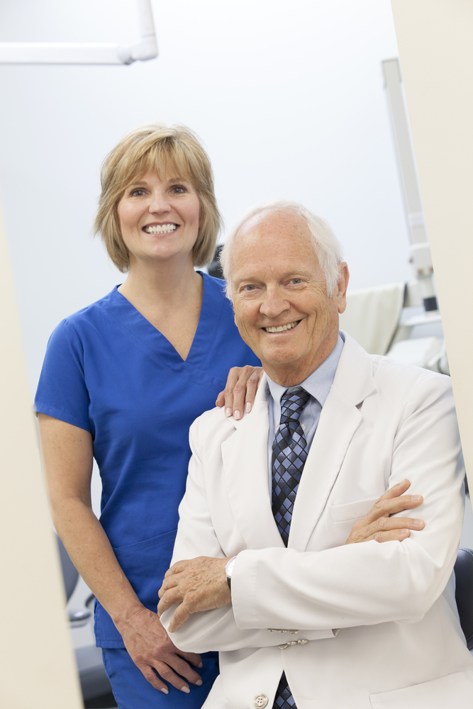 Environmental portrait of dentist & dental assistant smiling in modern office