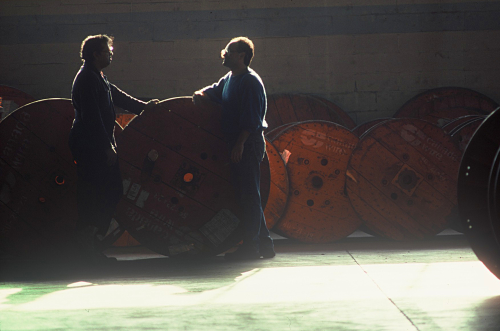 Colour Shot of Two Workers , Backlit and talking in Warehouse