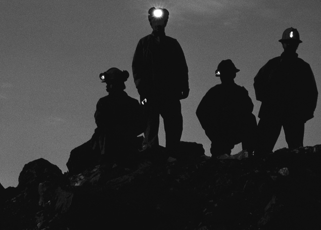 dramatic industrial black & white, Silhouette of miners standing on a rock