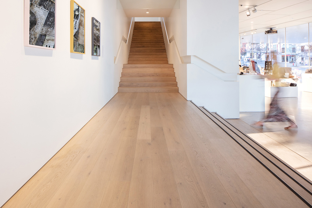 This modern interior photography shows a person in motion as she moves through the Polygon Gallery facility for fine art photography