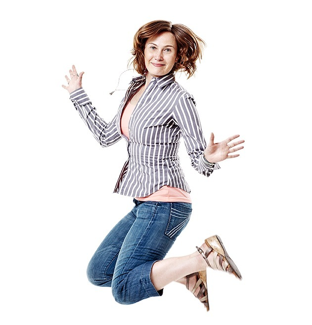 Dynamic shot of woman jumping in mid air against a white background